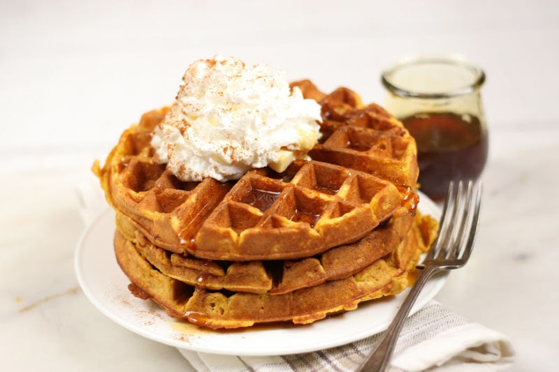 stack of waffles with syrup and whipped cream on top