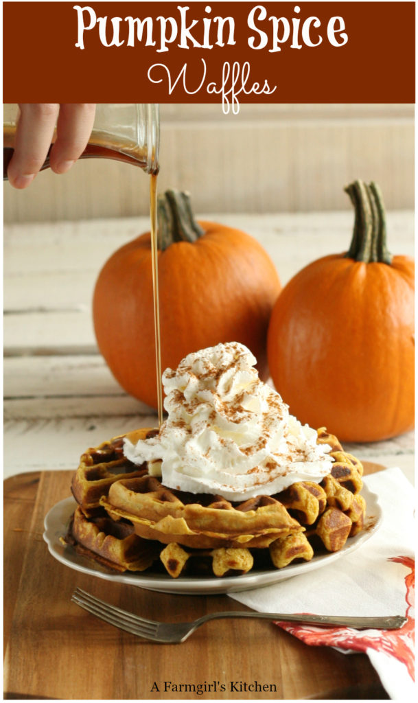 pumpin spice waffles stacked on a plate with whipped cream and dusted with ground cinnamon. Syrup being poured over top