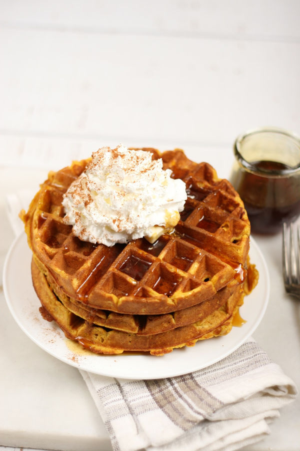 Pumpkin waffles stacked on plate with whipped cream, sprinkled with ground cinnamon