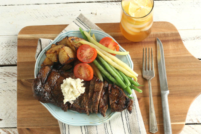 whiskey marinated steak sitting on a dish with fresh tomato slices, green beans, yellow wax beans and roasted potatoes