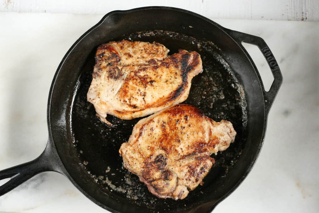 browning pork chops in a cast iron skillet