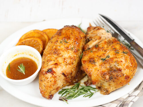 orange honey glazed chicken on a white plate with dipping sauce
