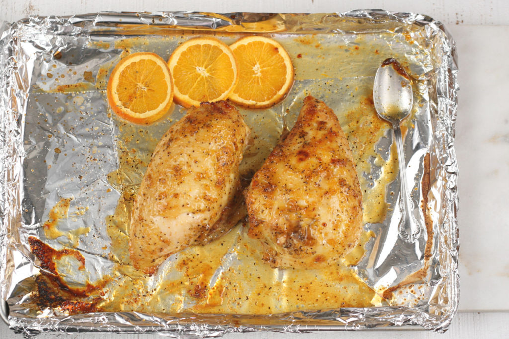 honey orange glazed chicken on a half sheet pan lined with aluminum foil and slices of oranges