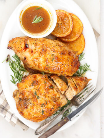 half breasts of chicken on a white serving plate with slices of oranges