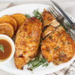 honey orange glazed half chicken breasts with slices of oranges on an oval white serving plate with fork and knife