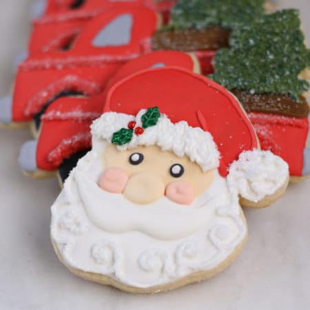 Santa face decorated sugar cookie with holly in his hat