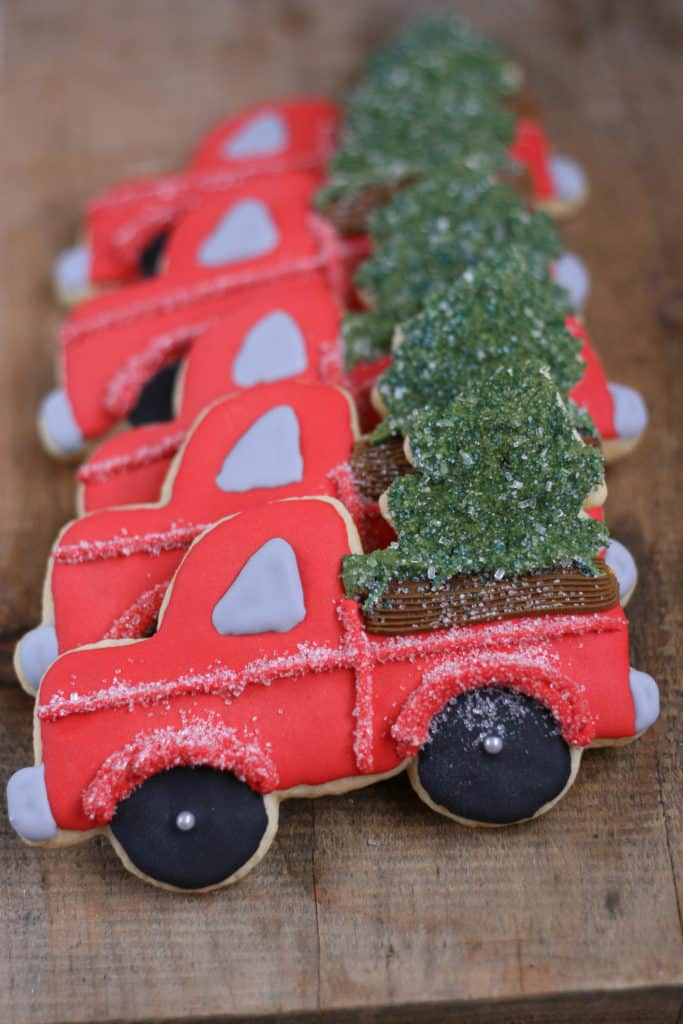 Decorated Sugar cookies vintage red trucks with Christmas tree in the back of the truck bed