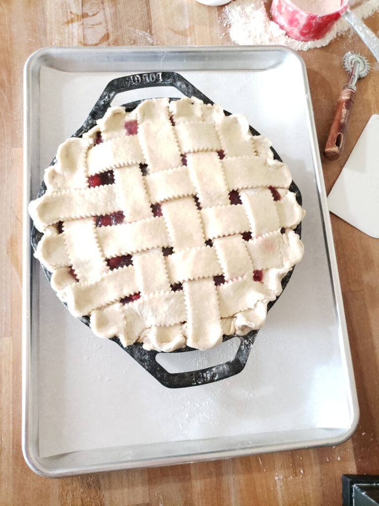 unbaked cherry pie in 2-handle cast iron skillet on a half sheet pan lined with parchment paper