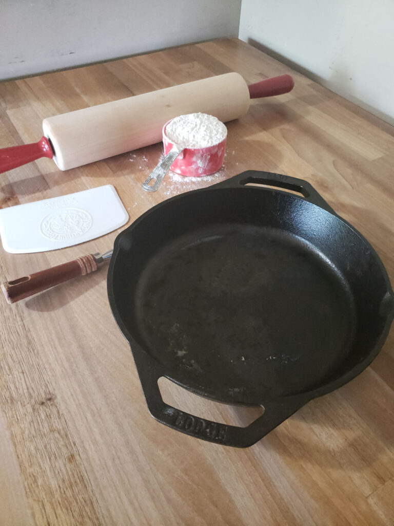 a 2-handle Lodge cast iron skillet on butcher block with wooden rolling pin with red handles