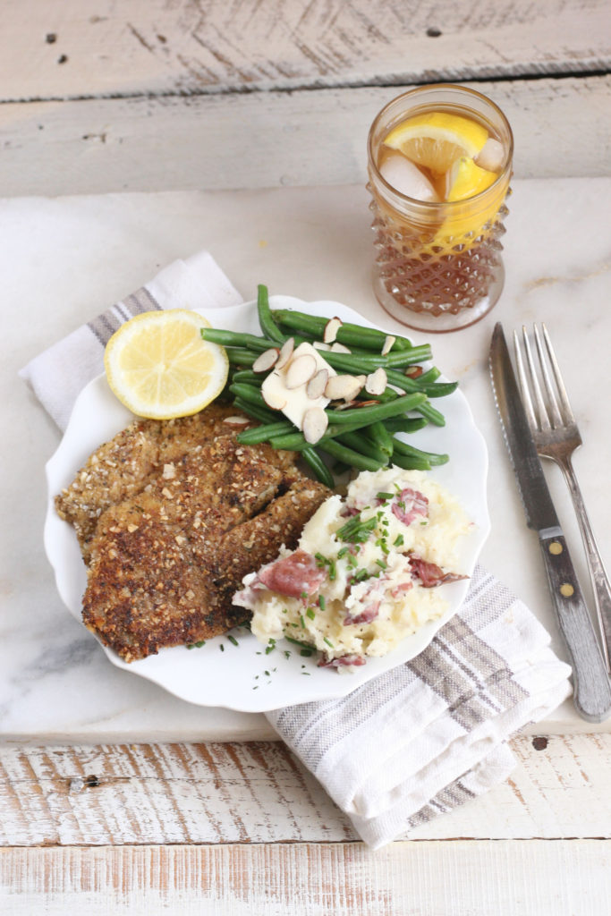 Almond crusted Talapia filets on a white plate with fresh green beans and smashed red potatoes