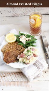 Almond crusted Tilapia filets on a plate with fresh green beans and smashed red potatoes