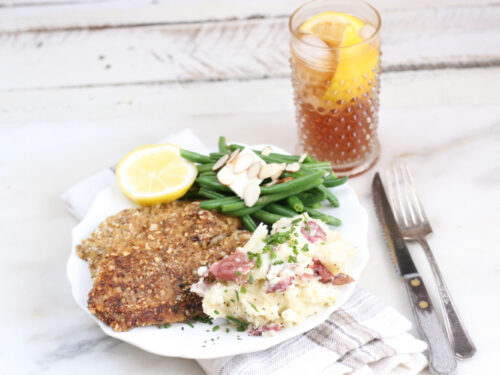 Almond crusted Tilapia filets with fresh green beans and smashed red potatoes on a white plate