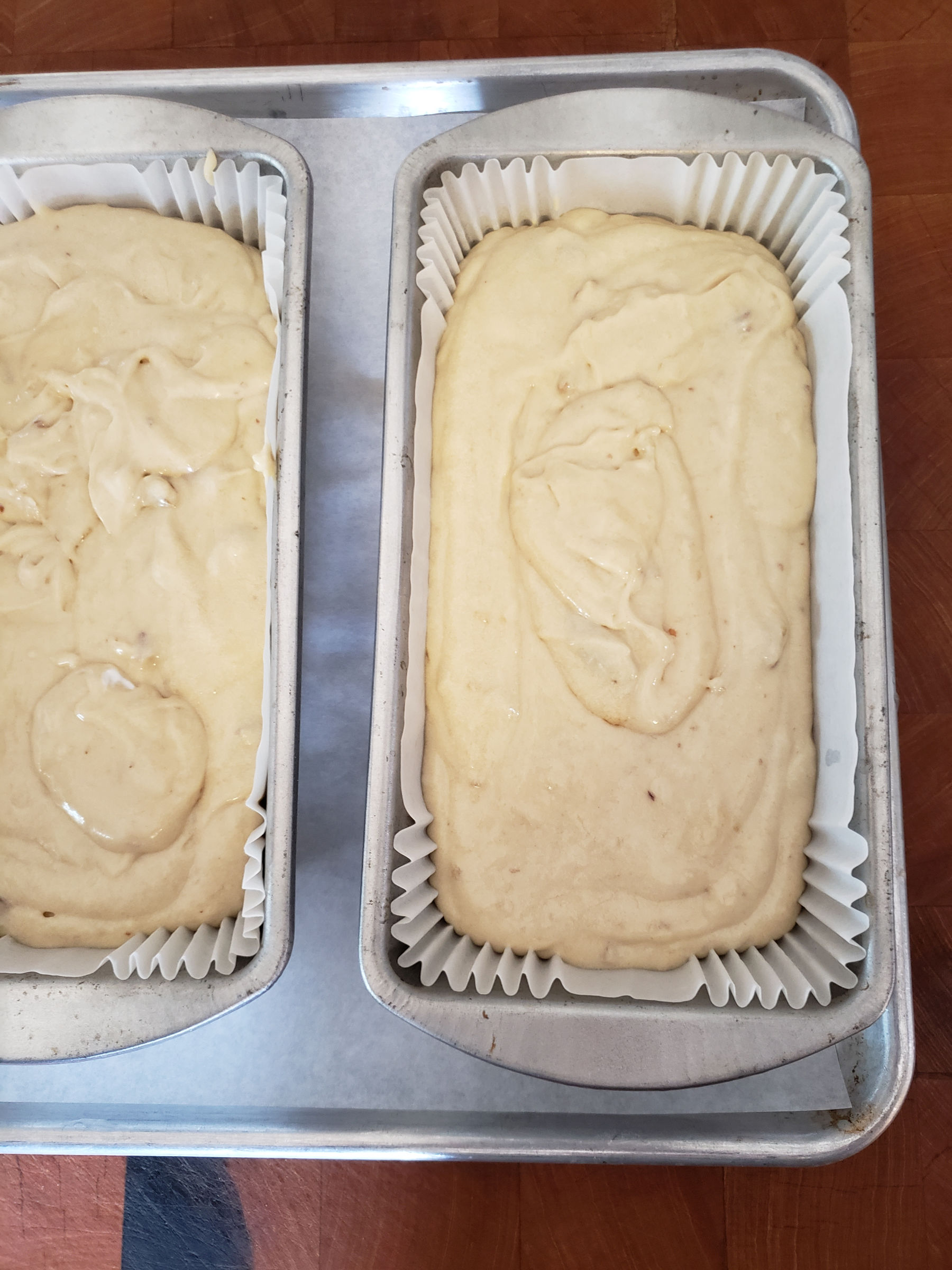 banana bread batter in loaf pans lined with paper liners.