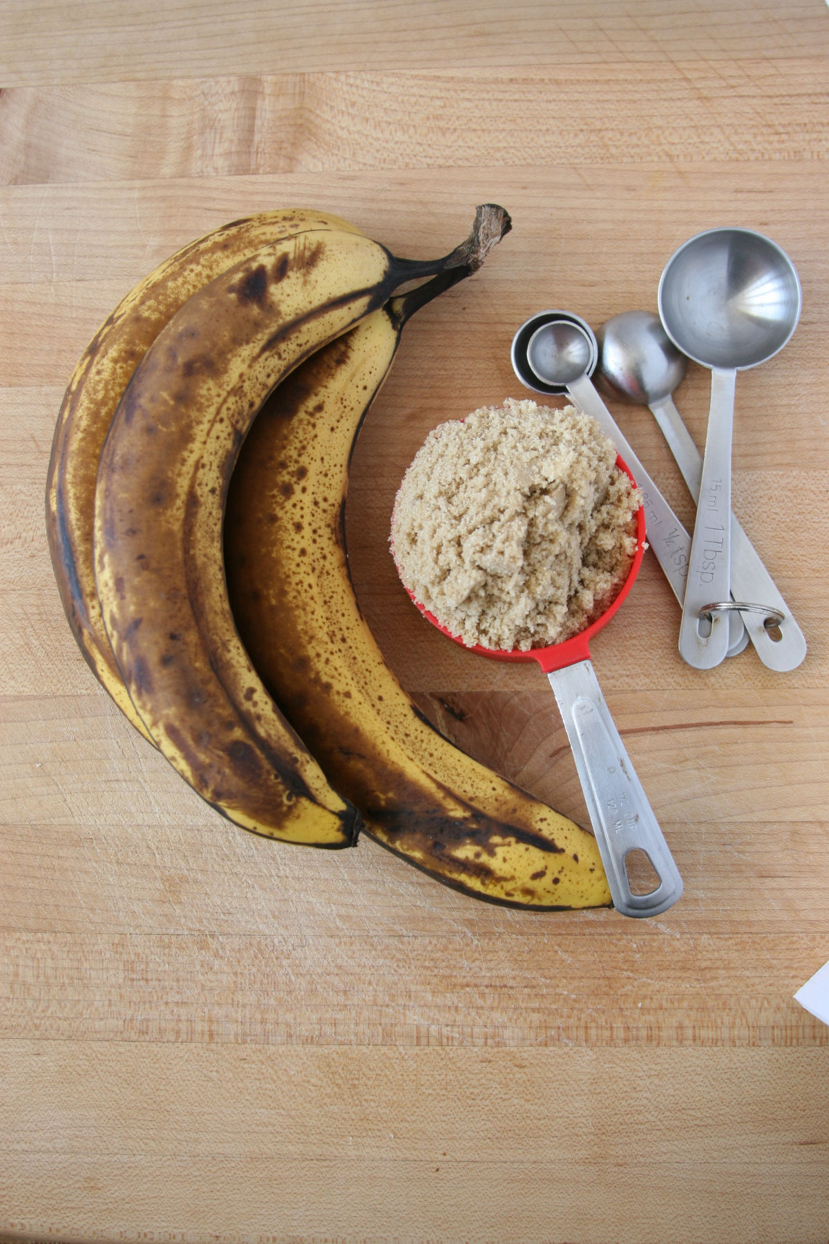 ripe bananas and a red measuring cup of brown sugar on a cutting board