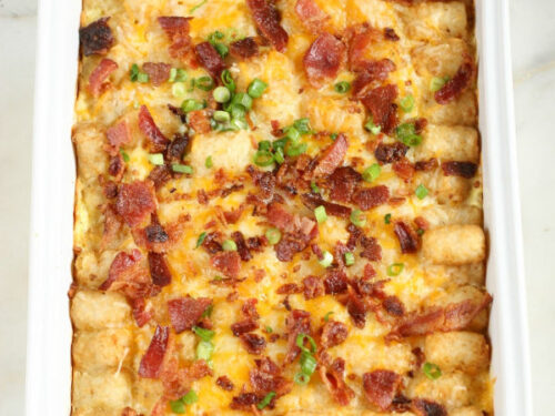 tater tots and bacon on top of a breakfast casserole in white casserole dish
