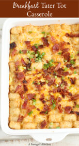 breakfast tater tot casserole in white ceramic casserole dish topped with crispy bacon pieces and shredded cheese