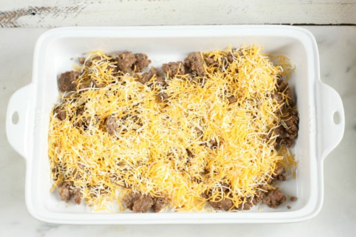rectangle white ceramic baking dish with cooked sausage and shredded cheese