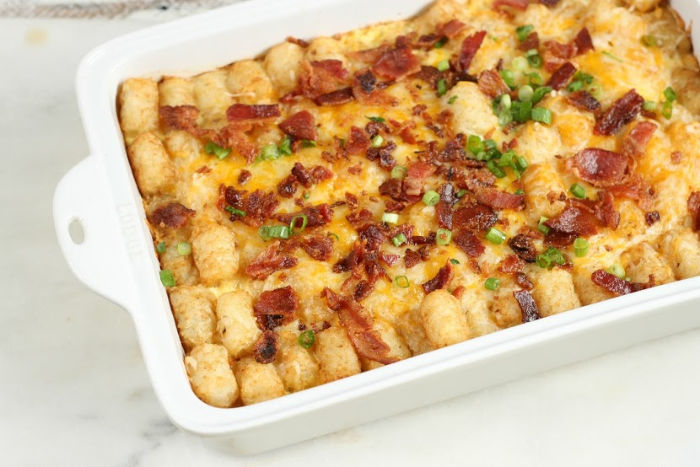 breakfast tater tot casserole in a white ceramic baking dish