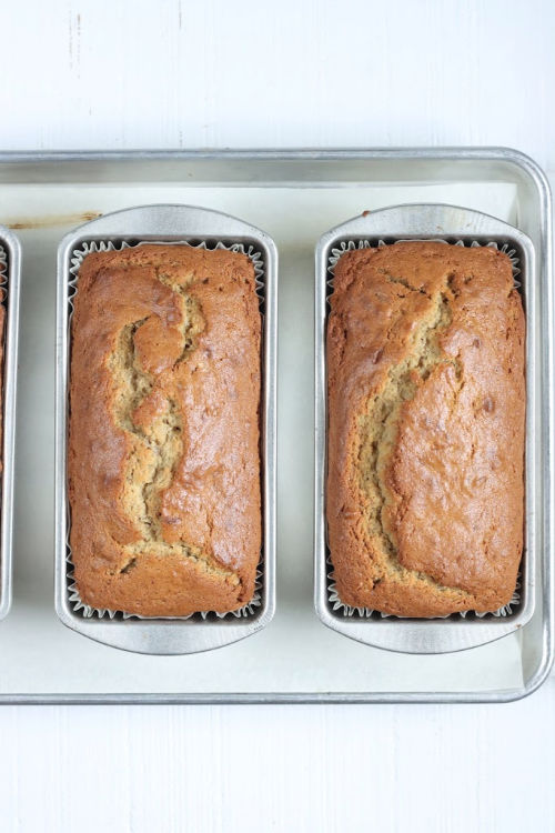 two loaves of banana bread in metal loaf pans cooling on baking rack