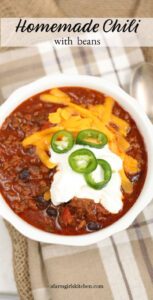 chili in a white bowl, topped with cheddar cheese, sour cream, and jalapeno slices