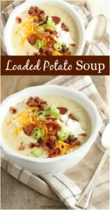 loaded potato soup in white bowl, topped with sour cream, crispy bacon, cheddar cheese, and green onion slices