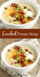 Homemde potato soup topped with pieces of crispy bacon, sour cream, shredded cheddar cheese, and thin slices of green onion