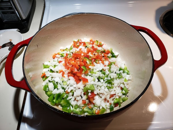 cooking chopped onions and bell peppers in a red Dutch oven