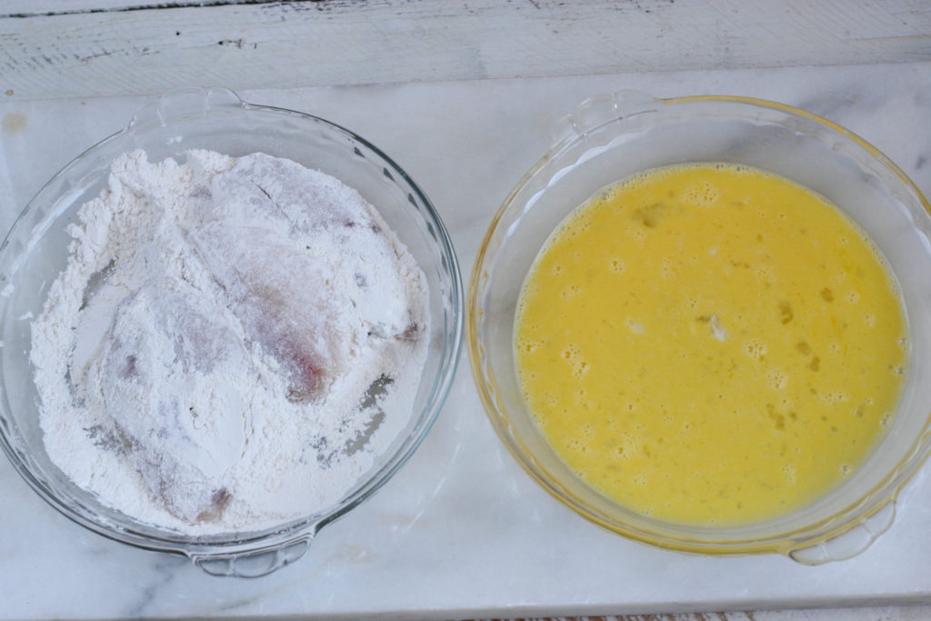Taliapa filets being coated with egg wash and flour