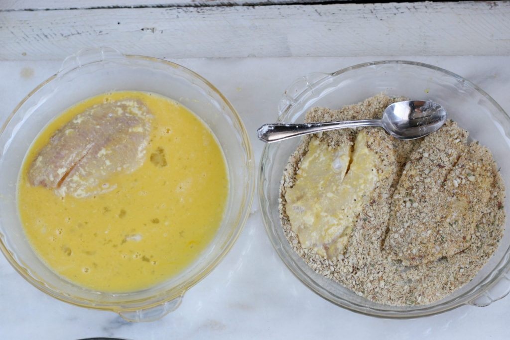 Tilapia filets being coated in egg wash and bread crumbs with crushed almonds