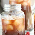 glass Mason jar with homemade iced tea, fresh raspberries surrounding on white reclaimed wood