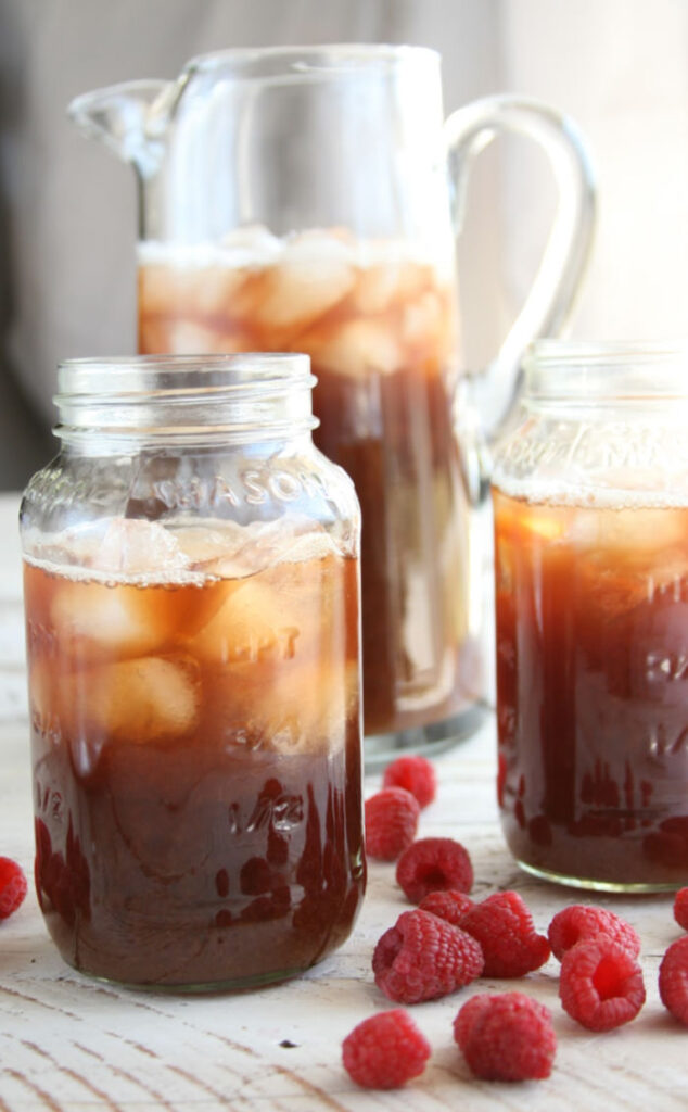 glass pouring pitcher with iced tea, Mason jars with ice and iced tea, loose raspberries surrounding