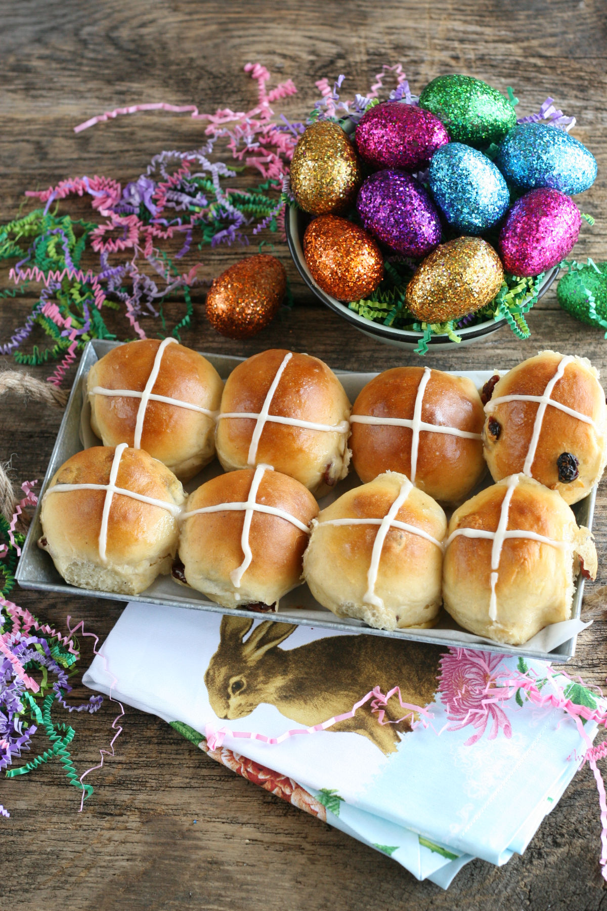 Hot Cross Buns with craisins lined up in a metal serving tray, colorful sparkled faux eggs in bowl.