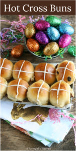 Hot cross buns with icing sitting in a galvanized tray and glittered Easter eggs to the background
