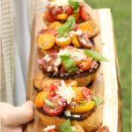 tomato bruschetta with cheese on wooden serving platter