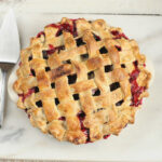 lattice pie crust on blackberry pie. on white marble with metal pie server to the left