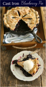 blueberry pie in a cast iron skillet, slice of pie with vanilla ice cream scoop on plate