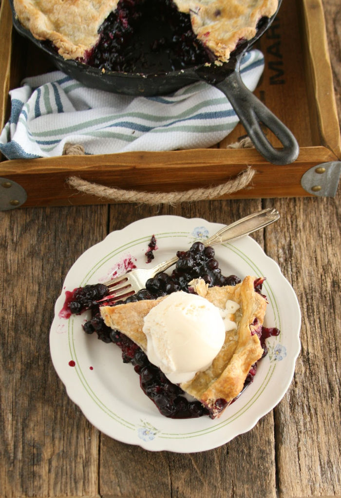 slice of blueberry pie with scoop of vanilla ice cream on scalloped white floral plate