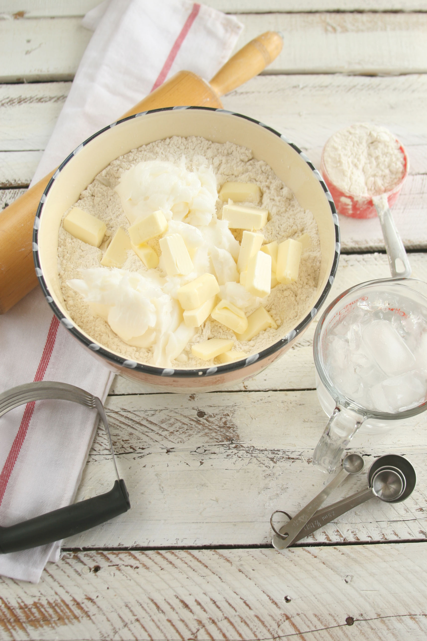 Ceramic bowl with flour, lard, and butter being cut in with a pastry cutter.