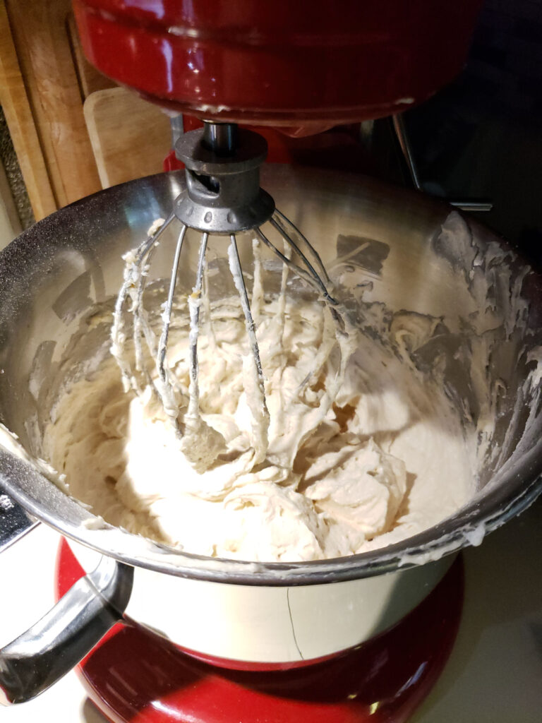 close up of beater in Red KitchenAid mixer with peanut butter frosting