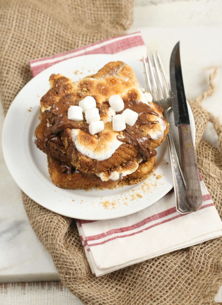 S'mores French Toast layered with toasted marshmallows and melted chocolate on a white plate