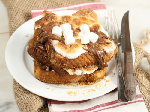 S'more French toast stacked on plate with toasted marshmallows and drizzled with Nutella Hazelnut spread