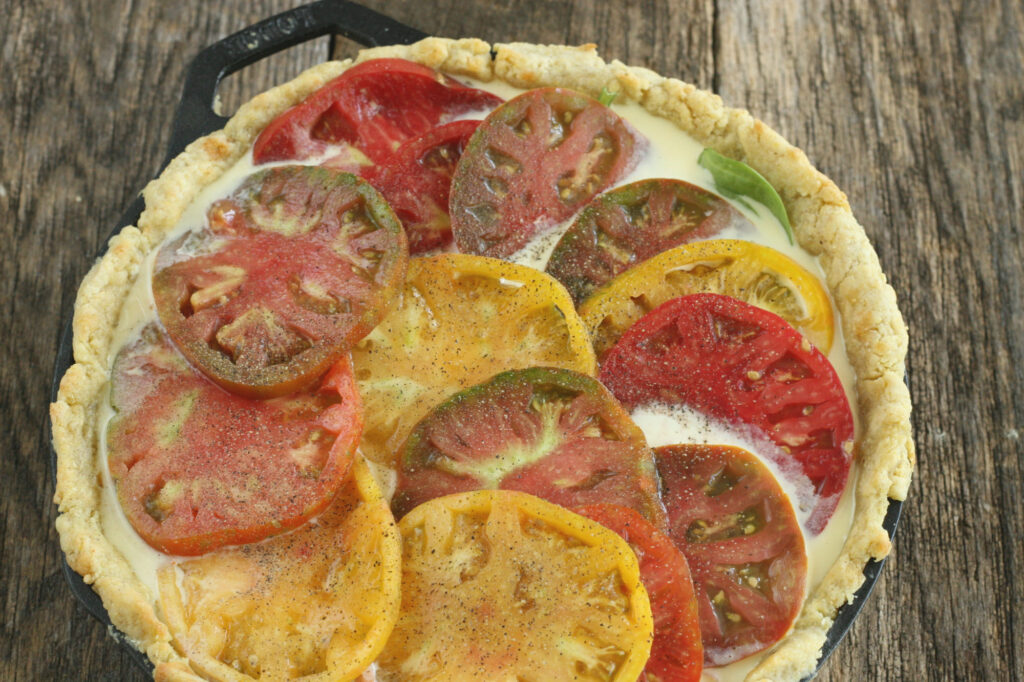 slices of heirloom tomatoes on top of an unbaked quiche in a cast iron skillet