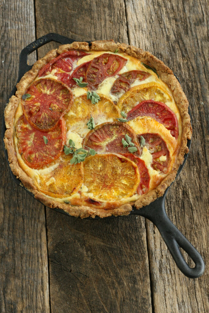 baked quiche in a cast iron skillet with heirloom tomatoes and spinach