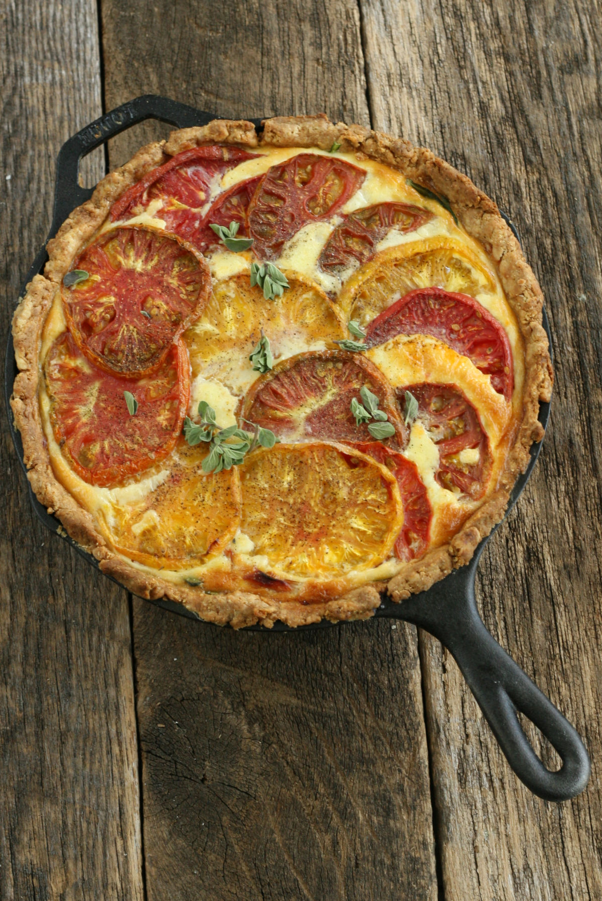 baked quiche in a cast iron skillet with heirloom tomatoes and spinach.
