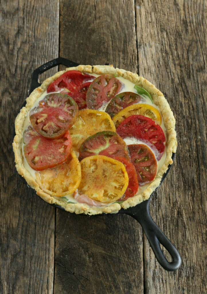 homemade quiche in a cast iron skillet on reclaimed barn boards