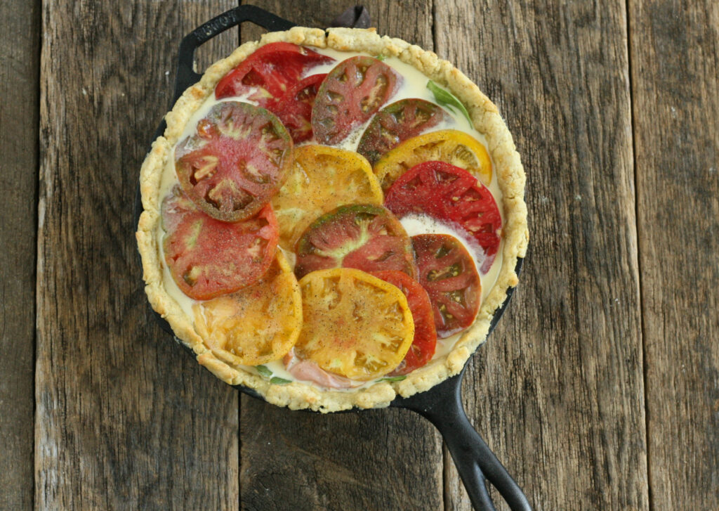 slices of heirloom tomatoes on top of a unbaked quiche with a cornmeal crust
