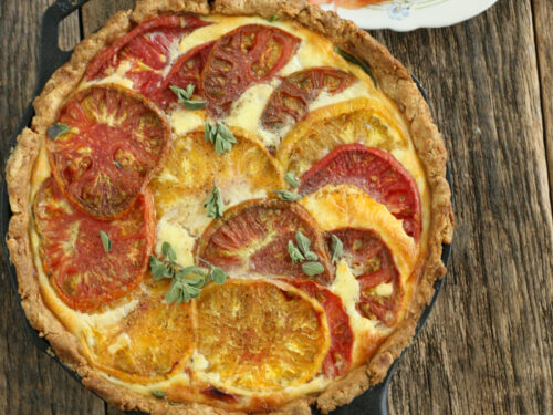 homemade quiche with heirloom tomatoes and spinach in a large cast iron skillet with a small glass plate of sliced tomoatoes near it