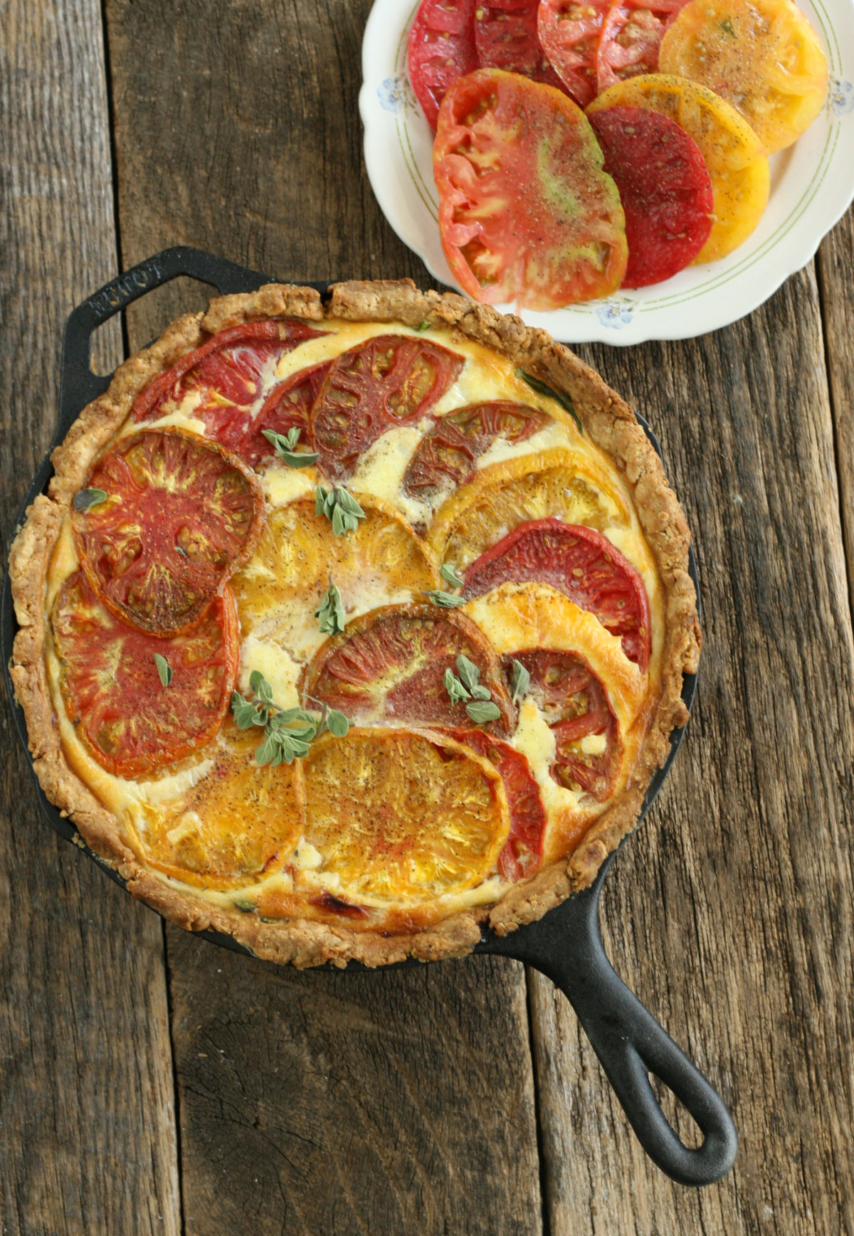 homemade quiche with heirloom tomatoes and spinach in a large cast iron skillet with a small glass plate of sliced tomoatoes.