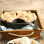 blueberry pie in cast iron skillet, slice of pie on plate with scoop of vanilla ice cream on top