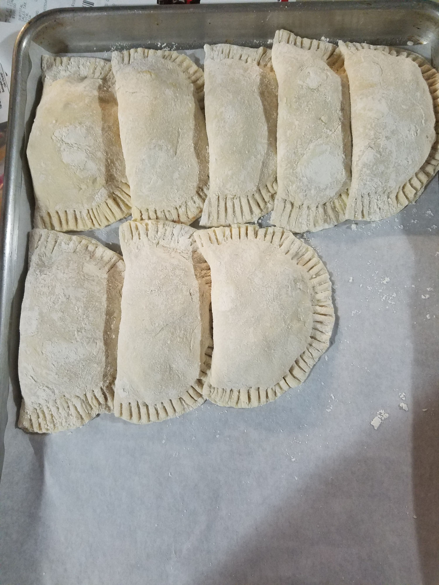 fried apple hand pies uncooked on a half sheet pan lined up against each other in three rows